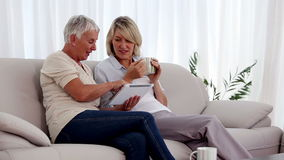 Mature women using tablet pc on the couch. While having a hot drink stock video footage