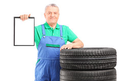 A mature worker on car tyres holding a clipboard. Isolated on white background Royalty Free Stock Photo