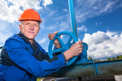 Mature worker with fitting valve Royalty Free Stock Images