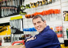 Mature Worker Leaning In Hardware Shop. Side view portrait of mature worker leaning in hardware shop Royalty Free Stock Image