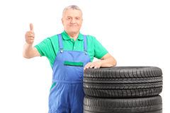 A mature worker posing on car tires and giving thumb up Royalty Free Stock Photos