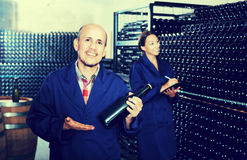 Mature worker in winery. Glad mature men holding bottle of bubble wine and standing in winery production section Stock Photo