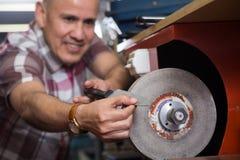 Mature workman resharpening knives on interlock spiral wheel sys. Senior workman resharpering knives on interlock spiral wheel system machine. Fokus on Knife Royalty Free Stock Image