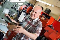 Mature workman sewing leather boots on stitch lathe Stock Image