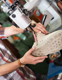 Mature  workman sewing leather boots on stitch lathe Stock Photos