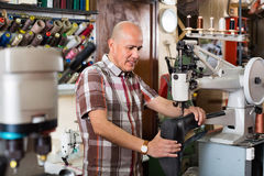 Mature  workman sewing leather boots on stitch lathe Stock Photography