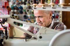 Mature workman sewing leather boots on stitch lathe Royalty Free Stock Photography