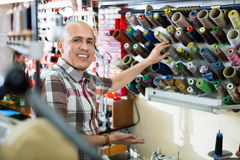 Mature workman sewing leather boots on stitch lathe Royalty Free Stock Images