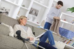 Mature wounded woman resting on sofa with carer Stock Images
