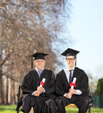 Mature and young college graduates in park Royalty Free Stock Images