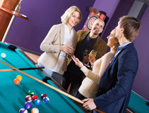 Mature and young couples hanging out in billiard club together Stock Photos