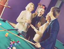 Mature and young couples hanging out in billiard club together Stock Photo