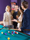 Mature and young couples hanging out in billiard club together Stock Photography
