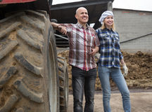 Mature and young farmers posing with old agrimotors in livestock Royalty Free Stock Photos