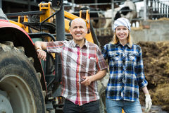 Mature and young farmers working at machinery Stock Photos