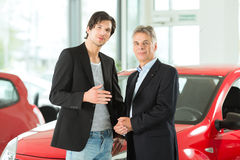 Mature and young man with autos in car dealership Royalty Free Stock Photo
