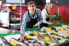 Mature and young sellers posing. Mature and young sellers working in fish section of market stock photography