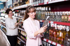 Mature and young women selecting bottle of vodka Royalty Free Stock Images