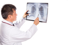 Matured Asian medical doctor examining lungs X-ray negative film Royalty Free Stock Photo