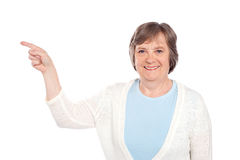 Matured casual lady pointing at copy space Royalty Free Stock Images