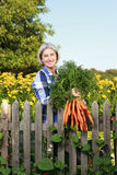 Matured farm woman with carrots Royalty Free Stock Image
