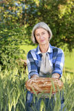 Matured farm woman with freshly baked bread Stock Photography