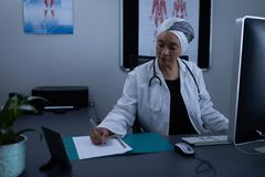 Matured female doctor writing on medical file in clinic. Front view of matured mixed race female doctor writing on medical file in clinic at hospital royalty free stock images