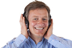 Matured man listening with headphones to mp3 music Stock Image