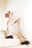 Matured man suffering acute knee joint pain climbing stairs.  royalty free stock image