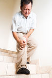 Matured man suffering acute knee joint pain descending stairs.  Stock Images