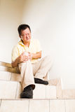 Matured man suffering acute knee joint pain seated on stairs.  stock photo