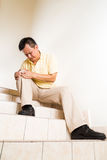 Matured man suffering acute knee joint pain seated on stairs Stock Photography