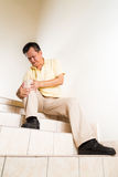 Matured man suffering acute knee joint pain seated on stairs.  royalty free stock image