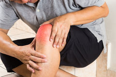 Matured man suffering painful knee joint seated on steps Royalty Free Stock Image