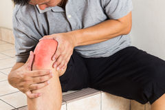 Matured man suffering painful knee joint seated on steps. Matured man suffering acute knee joint pain seated on staircase stock photo