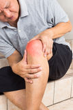 Matured man suffering painful knee joint seated on steps Royalty Free Stock Photo