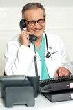 Matured physician communicating on phone Royalty Free Stock Images