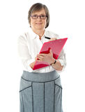 Matured professional woman writing on a red folder Royalty Free Stock Image