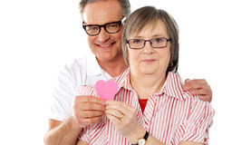 Matured smiling couple holding paper heart Royalty Free Stock Image