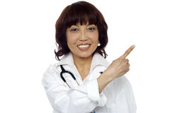 Matured surgeon pointing at the copy space Royalty Free Stock Image