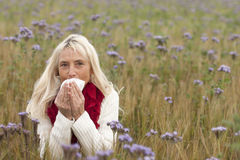 Matured woman with handkerchief  and allergy in a flower field Royalty Free Stock Images