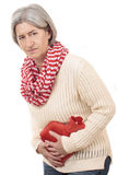 Matured woman with stomach pain and hot bottle Stock Image