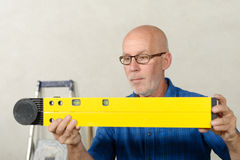A matureman with a spirit level Stock Image