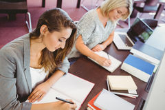 Matures females students writing notes at desk Royalty Free Stock Images