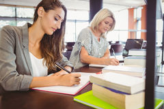 Matures females students writing notes at desk Stock Photography