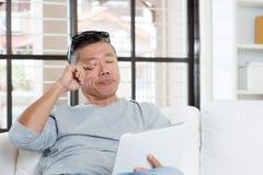 Maturi il dolore di occhi asiatico dell'uomo mentre per mezzo del computer della compressa immagini stock