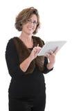 Maturi la scrittura attraente della donna di affari sul suo computer della compressa Fotografie Stock