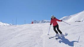 Maturi lo sciatore alpino della donna grassa che scolpisce professionale giù il pendio in montagne archivi video