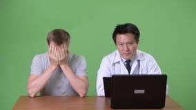 Maturi medico giapponese dell'uomo e giovane paziente avendo discussione archivi video