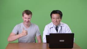 Maturi medico giapponese dell'uomo e giovane paziente avendo discussione stock footage